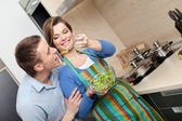 Woman offers her husband to taste salad with vegetable — Stock Photo