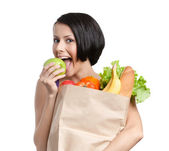 Lovely girl eats an apple,keeping the packet full of healthy food — Stock Photo