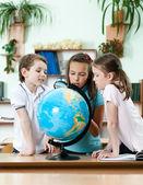 Friends stare at school globe — Stock Photo