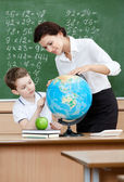 Geography teacher shows something to the pupil at the globe — Stock Photo