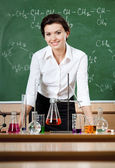Smiley chemistry teacher is surrounded with chemical instruments — Stock Photo