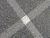 Abstract white painted cross on asphalt, industry details. — Stock Photo