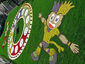 EURO 2012 talisman from flowers and green grass, clock in Kiev, Ukraine. — Stockfoto