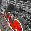Royalty-Free Stock Photo: Red round steam engine wheels and metal connected pipe heap.