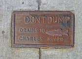 Do not dump drains to chales river as text on vintage surface. — Stock Photo