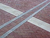 Abstract cross sign on red brick square, architecture details. — Stockfoto
