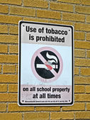Use of tabacco prohibited in all schools as message on sigbboard. — Stock Photo
