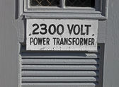 Power transformator 2300 volt as text on wooden signboard. — Stock Photo