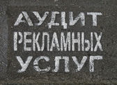 Advertising service audit as painted text on russian on asphalt. — Stock Photo