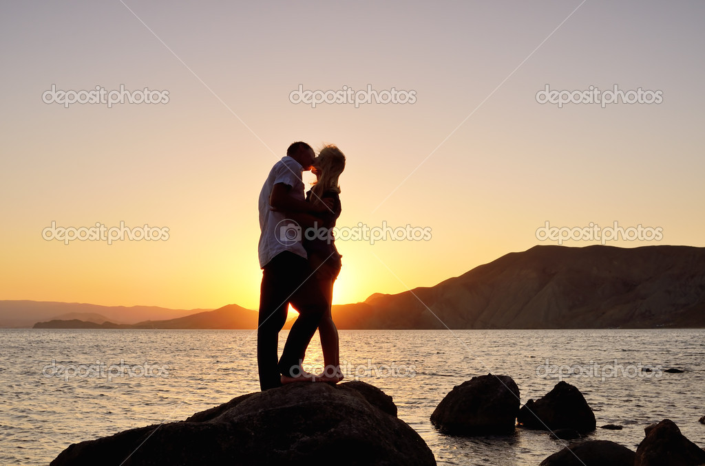 Young couple kissing by the sea at the setting sun — Stock Photo #12141488