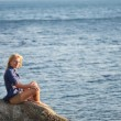 Royalty-Free Stock Photo: Girl is sitting on a rock near the sea