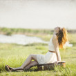 Young fashion girl with suitcase sitting at spring grass near lake. — Stock Photo #10762493