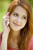 Redhead girl with mobile phone at the park. — Stock Photo
