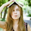 Girl with book over head. — Stock Photo