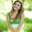 Beautiful teen girl in the park at green grass. — Stock Photo