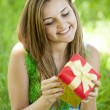 Beautiful teen girl with gift in the park at green grass. — Stock Photo