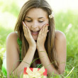 Surprised beautiful teen girl with gift in park at green gra — Stock Photo #11110657