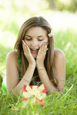 Surprised beautiful teen girl with gift in the park at green gra — Stock Photo