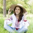 Slav teen girl at green meadow in national ukrainian clothing. - Stock Photo