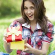 Beautiful teen girl with gift in park at green grass. — Stock Photo #11137976