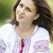 Stock Photo: Slav teen girl at green meadow in national ukrainiclothing.