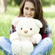 Stock Photo: Beautiful teen girl with Teddy bear in the park at green grass.