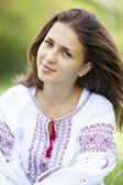 Slav teen girl at green meadow in national ukrainian clothing. — Stock Photo