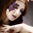 Style girl with makeup and violet flower. — Stock Photo