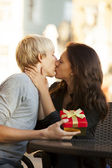 The young man and girl kissing in the cafe — Stock Photo