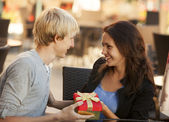 The young man gives a gift to a young girl in the cafe — Foto de Stock