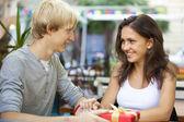 Il giovane dà un regalo per una ragazza giovane nel caffè — Foto Stock