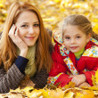 Mother and daughter in autumn yellow park — Stock Photo