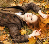 Portrait of red-haired girl in the autumn park. — Stock Photo