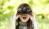 Teen girl with binocular at green grass — Stock Photo