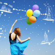Girl with colour balloons at blue sky background dreaming abut n — Stock Photo