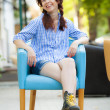 Funny hipster girl in chair on the street - Stock Photo