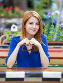 Style redhead girl sitting on the bench in the cafe — Stock fotografie