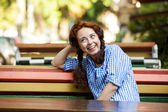 Grappige hipster meisje op de bank op de straat — Stockfoto