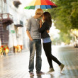 Young couple on the street of the city with umbrella — Foto Stock