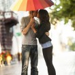 Young couple on the street of the city with umbrella — Stock Photo #11378892