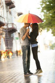 Young couple on the street of the city with umbrella — Stock Photo