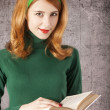 American redhead girl with book. — Stock Photo