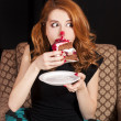 Stock Photo: Redhead girl secretly eating cake.