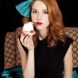 Redhead girl secretly eating cake. — Stock Photo