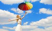 Flicka med paraply på himmel bakgrund. — Stockfoto