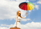 Beautiful redhead girl with umbrella and suitcase at blue sky ba — Stock Photo