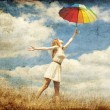 Girl with umbrella at meadow. — Stock Photo