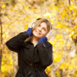 Girl with headphones at autumn park. — Stock Photo #11456699