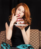 Redhead girl eating cake — Stock Photo