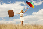 Beautiful redhead girl with umbrella and suitcase at outdoor. — Stock Photo